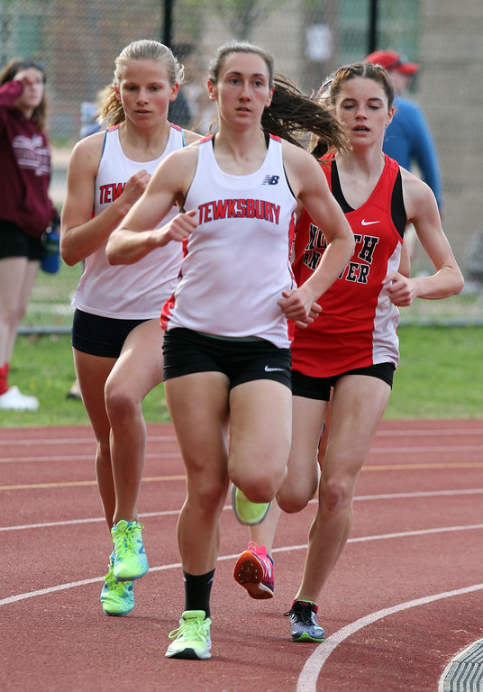. Tewksbury vs North Andover girls and boys track & field. From left, Tewksbury\'s McKenzie Clark and Rachel Sessa, and North Andover\'s Abby Mastromonaco, who trailed Sessa most of the way but won the Mile at the end. (SUN/Julia Malakie)