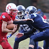 Tewksbury vs Wilmington Thanksgiving Day football. Tewksbury's Tyler Keough (23) is tackled by Wilmington's Yvenson Jeanty (52), left, and Stephen Smolinsky (41). (SUN/Julia Malakie)