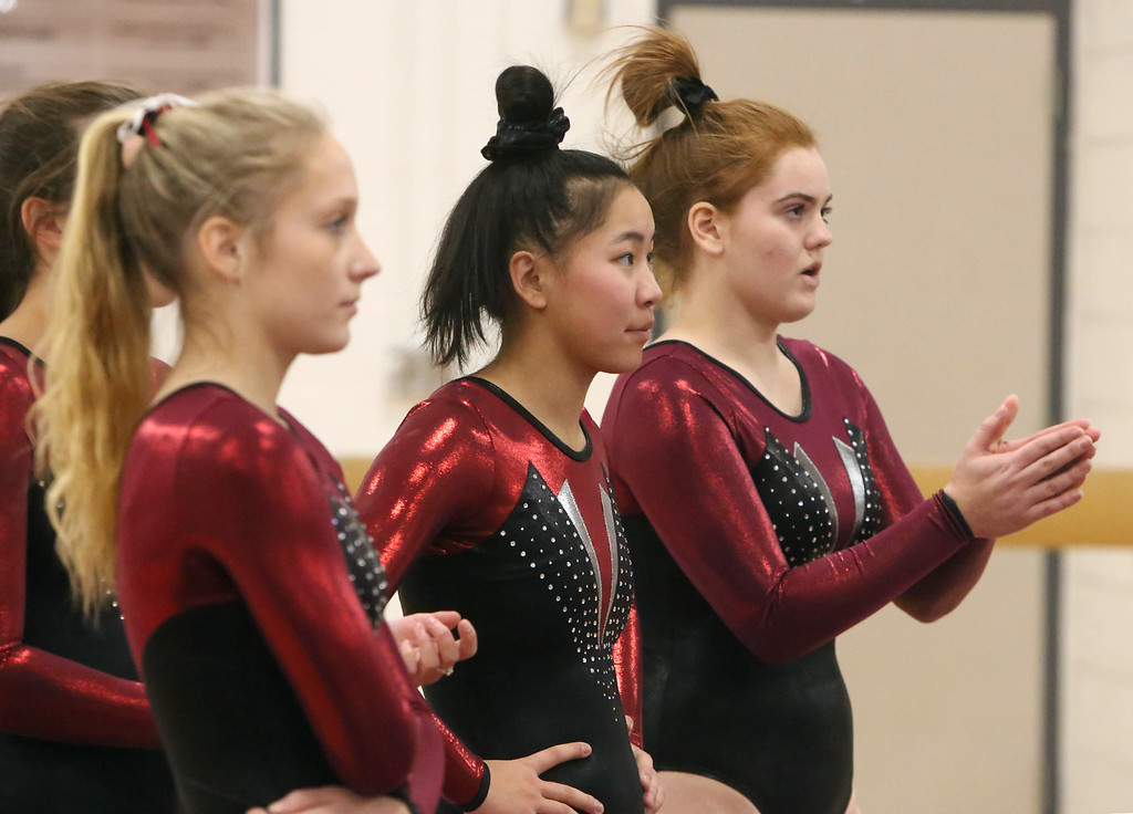 . Westford Academy vs Groton-Dunstable gymnastics. Groton-Dunstable\'s Nastia Subaciute, Kendra Antcil and Erin Woodle watch teammate on beam. (SUN/Julia Malakie)