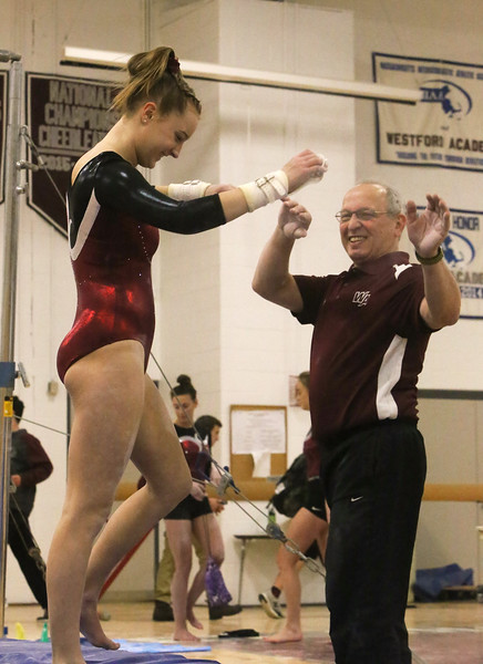 """Westford Academy vs Groton-Dunstable gymnastics. Grace Keele of Westford Academy and coach Tom Bonacci react after she finished her bars routine with a """"giants"""" on the third try. (SUN/Julia Malakie)"""