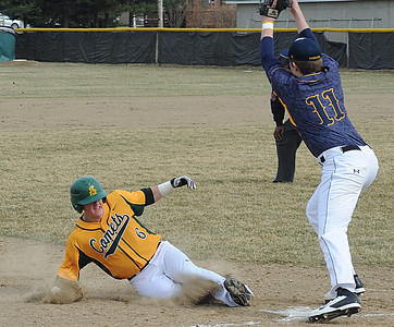 Amherst's Kody Bledsoe slides safe into third base before the throw to North Ridgeville's Nathan Colbert in the first inning. STEVE MANHEIM/CHRONICLE