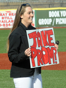 Elyria High student Ali Naogtte holds up a sign asking Elyria player Jake Csizmadia to the prom after she sang the national anthem. STEVE MANHEIM/CHRONICLE