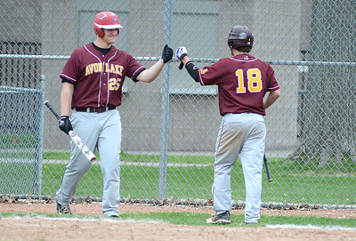 Avon Lake's Kyle Kuha and Jeramiah Campo celebrate Campo scoring a run against Elyria. KRISTIN BAUER | CHRONICLE