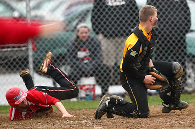 Brookside's Ryan Blotzer dives in safely at home as Black River catcher Brock Waltz checks out the other runners during the third inning Monday at Black River High School. Brookside overcame rainy conditions to win and hand the Pirates their first Patriot Athletic Conference loss of the year. AARON JOSEFCZYK/CHRONICLE