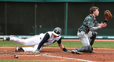 Elyria Catholic's Jeremy Smith slides into home plate safely as Highlands catcher Grant Loeding takes the throw.  AARON JOSEFCZYK/CHRONICLE