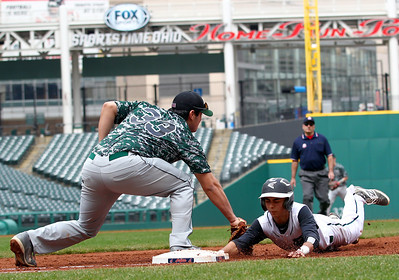 Elyria Catholic's Angelo Cruz dives back to first just ahead of the tag by Highland first baseman Yanni Patten.  AARON JOSEFCZYK/CHRONICLE