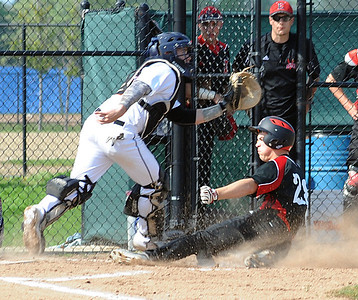 Elyria's Jaeger Shaffstall makes it into home safely as North Olmsted catcher Joe Keleman reaches for the ball in the second inning of Tuesday's Division I sectional opener at Victory Park. Elyria won. STEVE MANHEIM/CHRONICLE