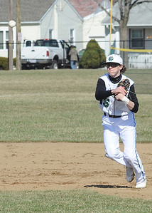 Elyria Catholic's Lukas Redmond makes a throw to first base. STEVE MANHEIM/CHRONICLE