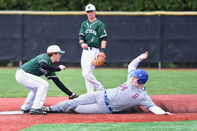 KRISTIN BAUER | CHRONICLE Elyria Catholic High School shortstop Tony LoParo (5) tags out Bay High School's Thomas Koss (34) as Koss slides into second on Tuesday afternoon, May 2. Elyria Catholic second baseman Ryan Strittmather (4) provides backup.