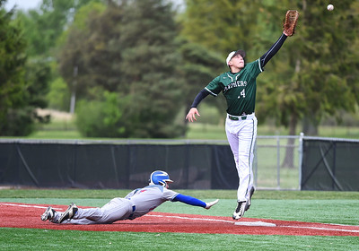 KRISTIN BAUER | CHRONICLE Bay High School's Logan LaMere (17) slides back into first as Elyria Catholic High School first baseman Jack Laird (14) jumps to catch an overthrown ball on Tuesday afternoon, May 2. LaMere was able to steal both second and third after the error.