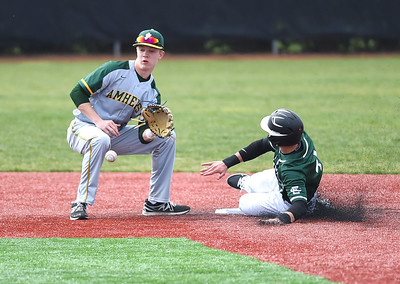 KRISTIN BAUER | CHRONICLE Amherst Steele High School shortstop Ryan Glowacki (9) attempts an out at second, but cannot secure the ball in time as Elyria Catholic High School Ryan Strittmather (4) slides safely into second on Sunday afternoon, April 2.