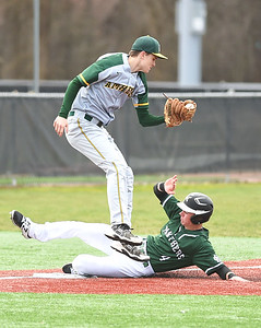 KRISTIN BAUER | CHRONICLE Elyria Catholic High School's Ryan Strittmather (4) slides safely into third as Amherst Steele High School third baseman Gehrig Gabrie (8) fails to secure the ball in time on Sunday afternoon, April 2.