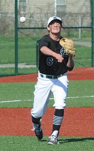 Elyria Catholic's Brendan Holley throws to first base at League Park on April 18.  STEVE MANHEIM / CHRONICLE