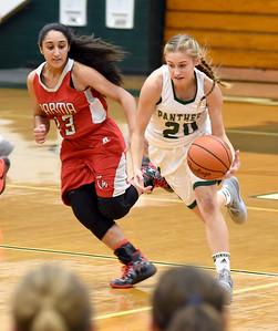 KRISTIN BAUER | CHRONICLE          Elyria Catholic High School senior Hailey Zanin (21) takes the ball down the court and is followed by Parma High School junior Jaylin Narvaez (13) on Wednesday night, Dec. 9.