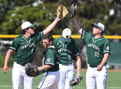 KRISTIN BAUER | CHRONICLE Elyria Catholic High School shortstop Tony LaParo (5) high-fives teammate first baseman Michael Nedwick (12) as catcher Grant McClure (10) and pitcher Andrew Abrahamowizc (9) duck below during a game against Lutheran West on Tuesday afternoon, May 16.