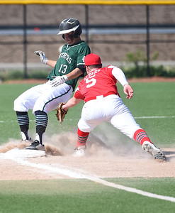 KRISTIN BAUER | CHRONICLE Elyria Catholic High School's Jeff Spencer (13) narrowly avoids a tag out at third by Lutheran West High School third baseman Owen Albers (5) on Tuesday afternoon, May 16 after hitting a triple.
