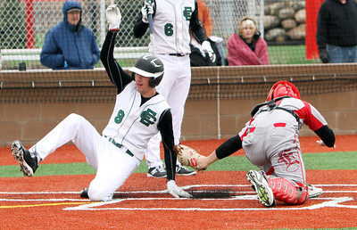 ANNA NORRIS/CHRONICLE Elyria Catholic's Andrew Abrahamowicz avoids the tag at home from Elyria catcher Seth France to score a run in the first inning at Sports Force Field in Sandusky Saturday morning.