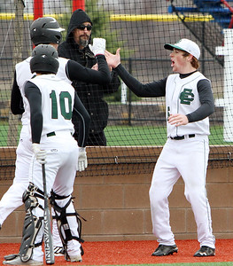 ANNA NORRIS/CHRONICLE Elyria Catholic's Tony LoParo (5) high fives Andrew Abrahamowicz after scoring on an Elyria error in the first inning Saturday morning at Sports Force Field in Sandusky.