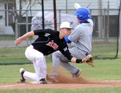 Brunswick Kyle Michalik slides safe at third and scores on a bad throw to Elyria's Troy Goscewski in first inning Apr. 10.   Steve Manheim