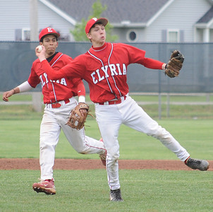 Elyria Justin Murray makes an off-balance throw to first base , in front of Derrick Monk May 12.  North Olmsted runner was safe.  Steve Manheim