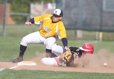 North Ridgeville's third basemen Matt Feierabend goes flying as he is hit by Elyria's #11Tony Pierce, who was called safe.