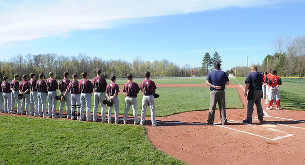 Wellington and Firelands baseball teams stand for the national anthem at the new Larry DeVoe Memorial Field in Wellington on April 17.