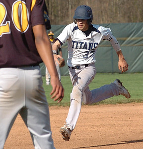 Lorain's #37 Adrian Calez safely runs for third base as Cleveland heights pitcher #20 Aaron Stanich backs up the third baseman.