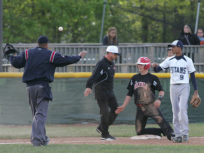 Elyria's #5 Troy Goscewski is congratulated at third for hitting a triple; Titan #9 is Antoine Edwards.        photo by Chuck Humel