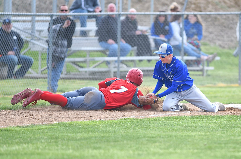 KRISTIN BAUER | CHRONICLE Midview High School third baseman Jacob Landers (10) tags Elyria High School's Devan Nail (7) out at third after Nail rounded third slipped and tried returning to third on Friday afternoon, May 12.