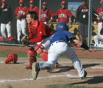 Midview's #1 Ben Simkovich will slide wide — although he didn't have to — of Elyria Catcher Steve Poskocil who is waiting for a throw from the field.     photo by Chuck Humel