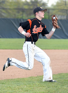 KRISTIN BAUER | CHRONICLE North Olmsted High School third baseman Greg Helderman (7) charges a ground ball while playing a game against North Ridgeville High School on Wednesday evening, May 11.