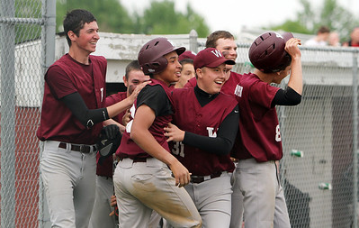 Jujuan Howard, center, celebrates with the rest of the Wellington Dukes team after beating Oberlin in extra innings 5-4 in sectional play yesterday at Wellington High School. (CT photo by Anna Norris.)