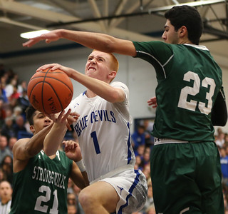 Brunswick's Kyle Goessler is fouled by Strongsville's Brandon Kagan (21) as Shaun Csire also defends during the first half. AARON JOSEFCZYK / GAZETTE