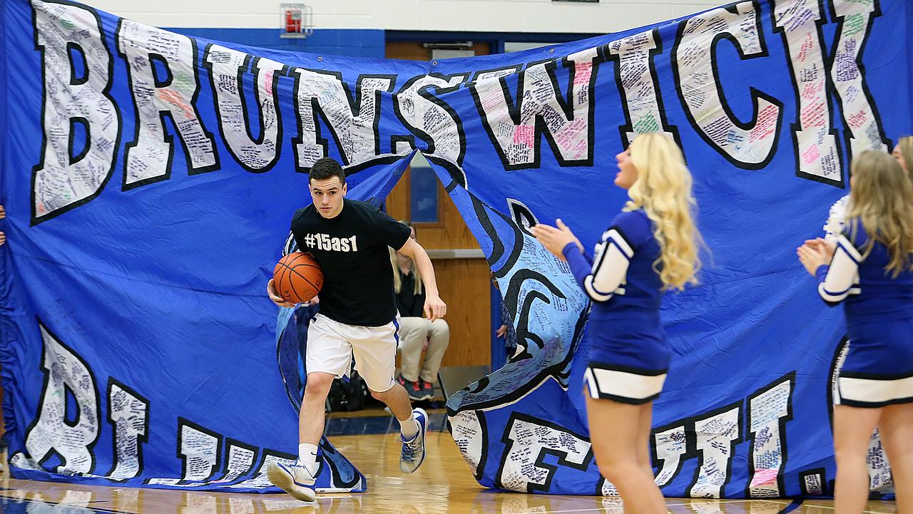 Brunswick's Ryan Flynn leads the team onto the court against Shaker Heights. (RON SCHWANE / GAZETTE)