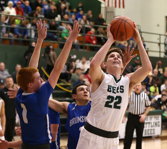Medina's Luke Schaefer puts up a shot past Brunswick's Kyle Goessler during the first half. AARON JOSEFCZYK / GAZETTE