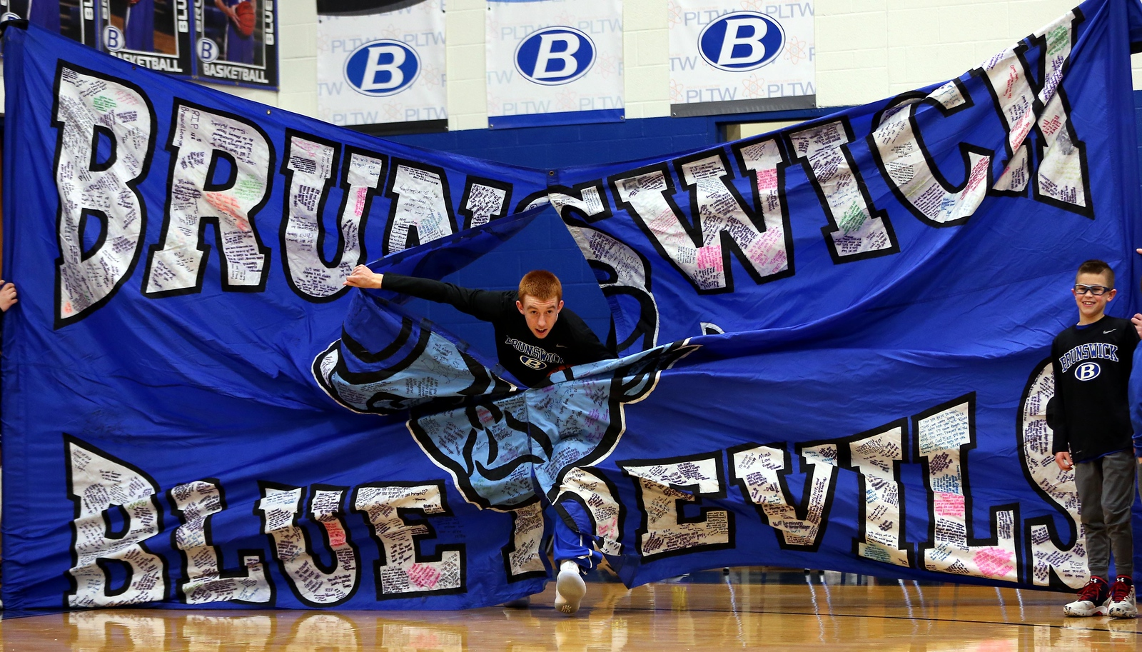 Kyle Goessler breaks through the banner prior to the start of the Blue Devils game against Elyria. AARON JOSEFCZYK / GAZETTE