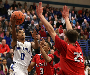 Brunswick's Keith Simmons puts up a shot over  Elyria's Josh Lotko and Michael Oliver during the first quarter. AARON JOSEFCZYK / GAZETTE