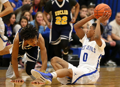 Brunswick's Keith Simmons looks to pass as he sits on the court defended by Euclid's Emari Baddour during the second quarter. AARON JOSEFCZYK / GAZETTE