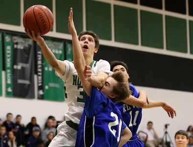 Highlands' Collin Rittman puts up a shot with some heavy contact from Reveres' Kyle Tretter during the first half. Aaron Josefczyk/Gazette