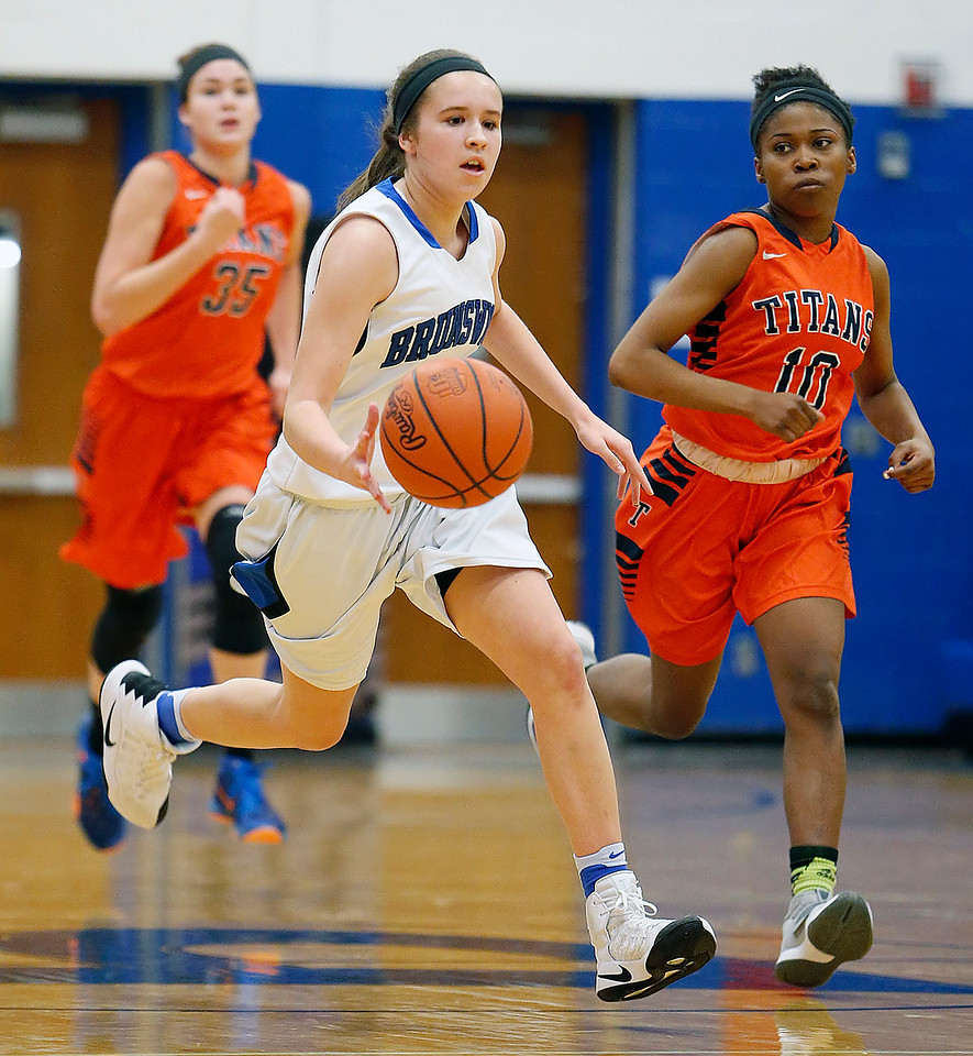 Brunswick's Angela Fink pushes the ball up the court past Berea-Midpark's Miranda Otero (35) and Jada Marone during the first quarter. (RON SCHWANE / GAZETTE)