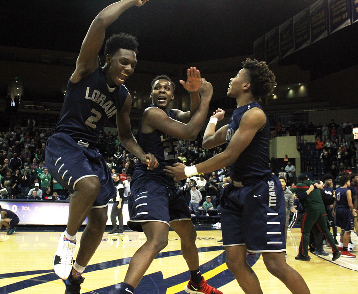 ANNA NORRIS/CHRONICLE<br /> Lorain's Taevon Pierre-Louis, Jaiden Sledge and Jordan Jackson celebrate after beating Toledo St. John-Jesuit 47-44 in the Division I regional championship game, advancing to the state tournament in Columbus, at the John A. Savage Arena at the University of Toledo Saturday afternoon.