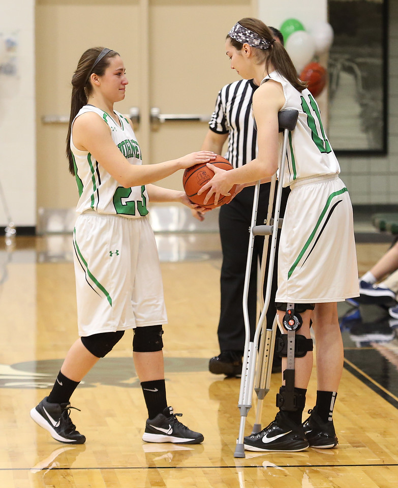 Highland's Sam Catron hands the ball to teammate Marlee Profitt just after tipoff. Profitt, who is recovering from ACL surgery, was allowed to participate in a ceremonial tipoff. AARON JOSEFCZYK/GAZETTE