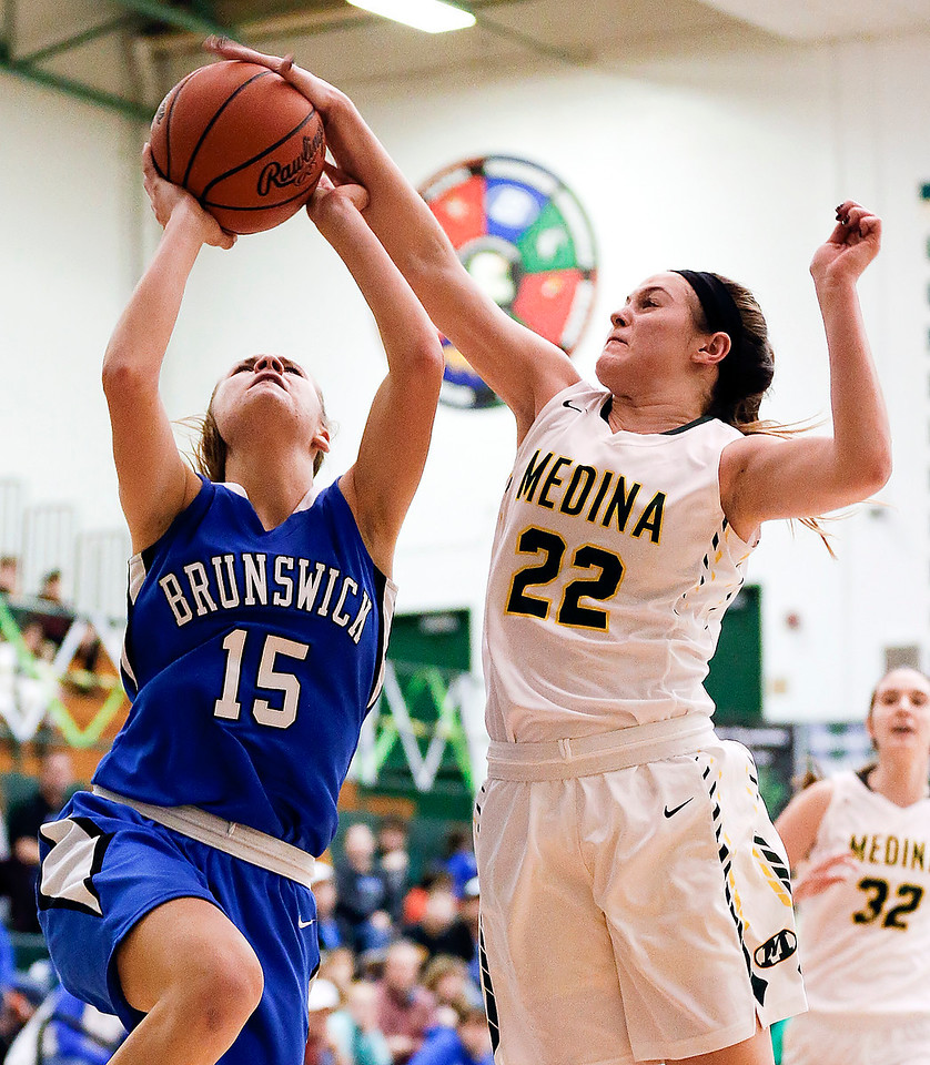 Medina's Anna Marie Smith blocks a shot by Brunswick's Maddy Grabowski during the second quarter. (RON SCHWANE / GAZETTE)