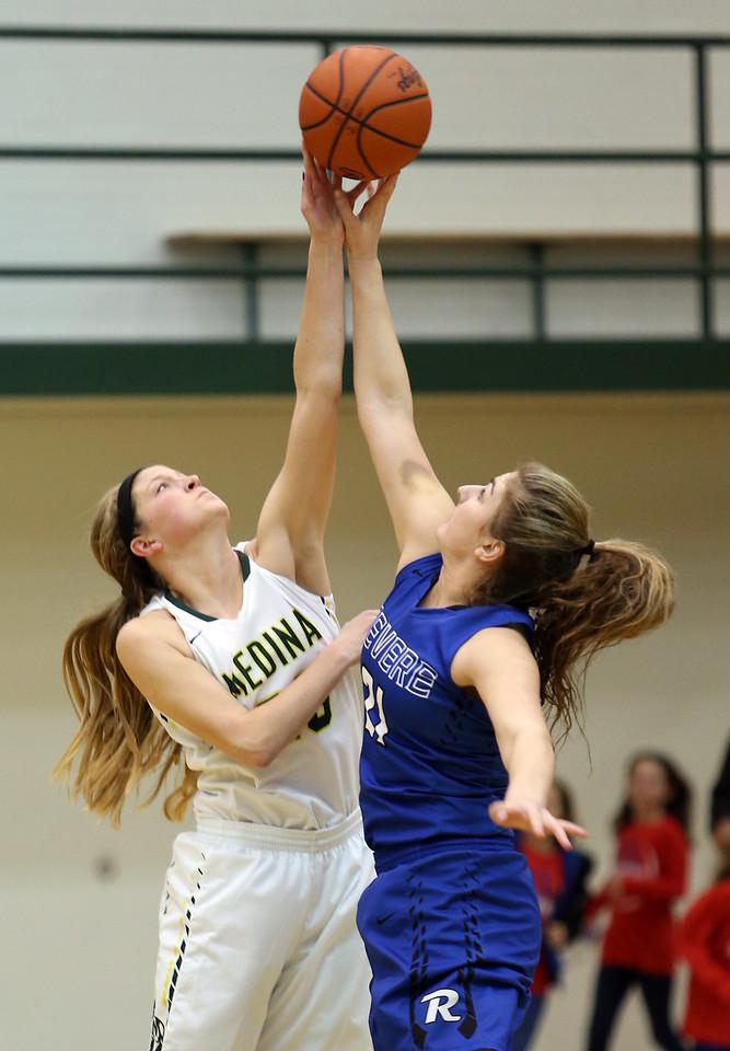 Medina's Jessie Holzman battles Reveres Viktoria Farian for the opening tip. AARON JOSEFCZYK/GAZETTE