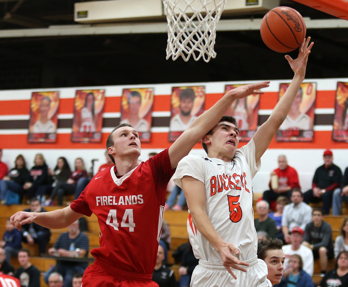 Buckeye's Braeden Stauffer is able to get his shot up and in around the reach of Firelands' Colin Meyers during the first half. AARON JOSEFCZYK/GAZETTE