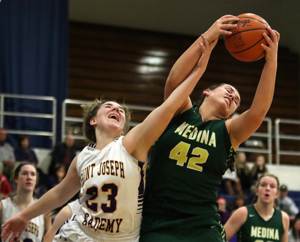 Medina's Emma Bobey grabs a first half rebound over Saint Joseph's Kathleen DeCarlo. AARON JOSEFCZYK/GAZETTE