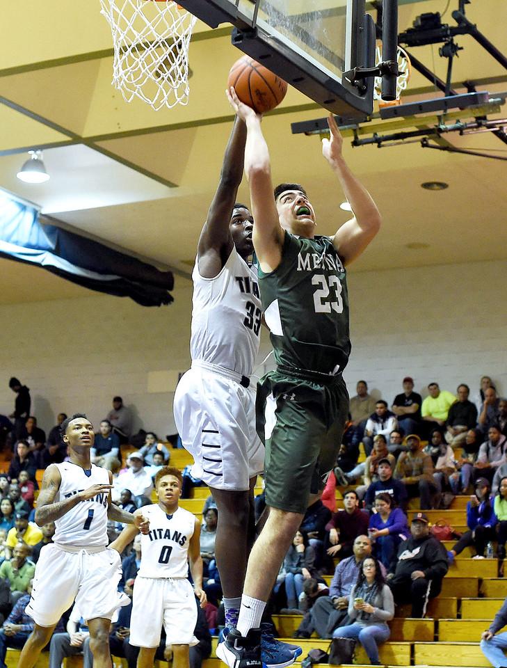 KRISTIN BAUER \ GAZETTE Medina High School junior Jimmy Daw (23) jumps to take a shot as Lorain High School junior Naz Bohannon (33) guards him on Tuesday night, Jan. 19.