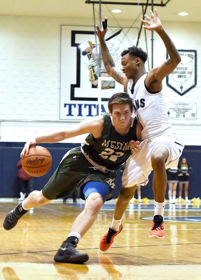 KRISTIN BAUER \ GAZETTE Medina High School junior Luke Schaefer (22) presses towards the hoop as he is guarded by Lorain High School senior Daviere Andrews (1) on Tuesday night, Jan. 19.
