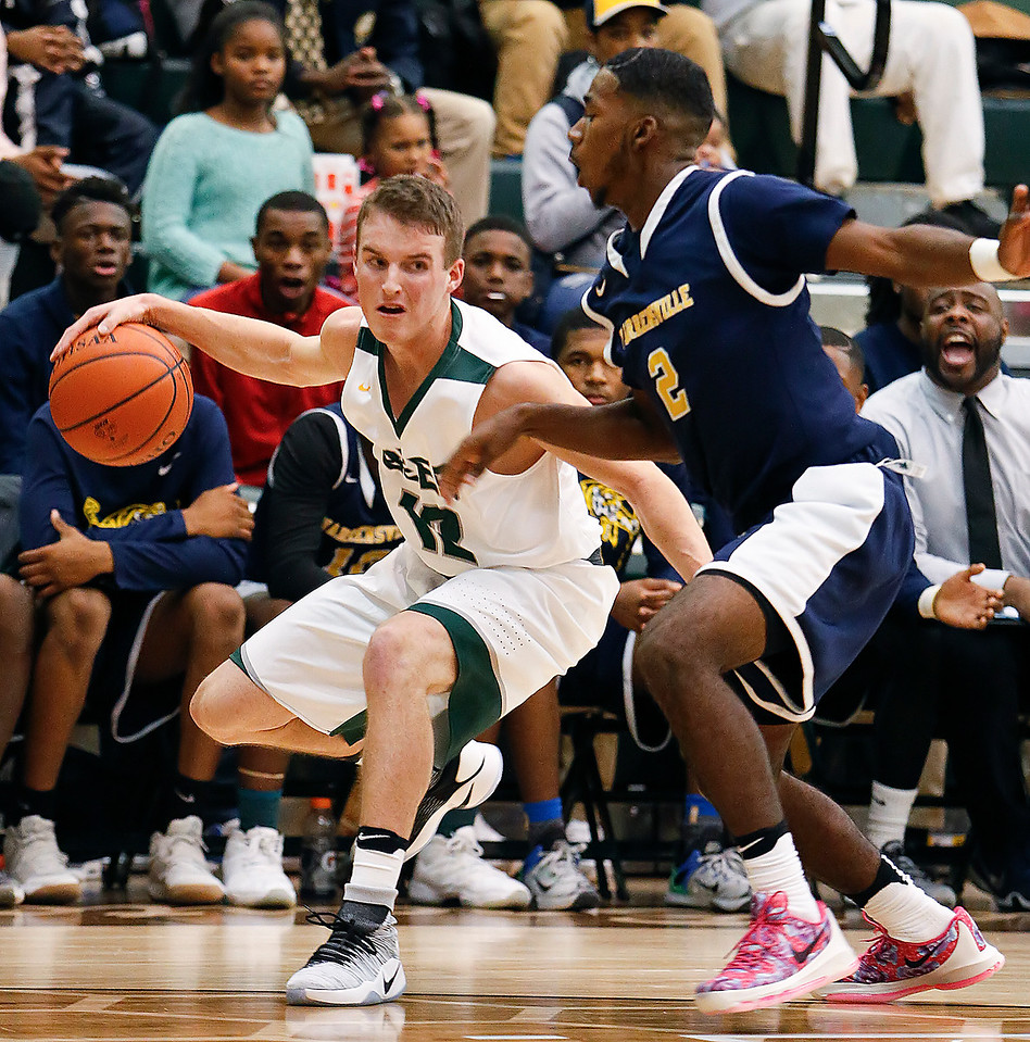 Medina's Jackson Sartain drives against Warrensville's Sha'Mar Latham during the first quarter. (RON SCHWANE / GAZETTE)