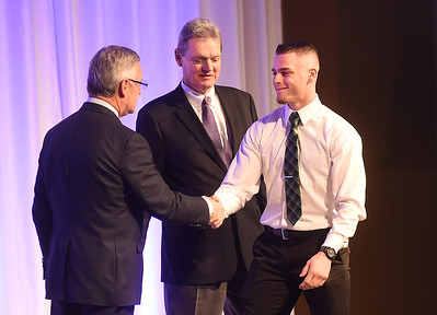 KRISTIN BAUER | CHRONICLE   Marion L. Steele High School running back Jeremy Smith shakes the hands of Jim Tressel and Larry Kehres on Tuesday night, March 7 during the Mike Cleary Northeastern Ohio Chapter of the National Football Foundation.
